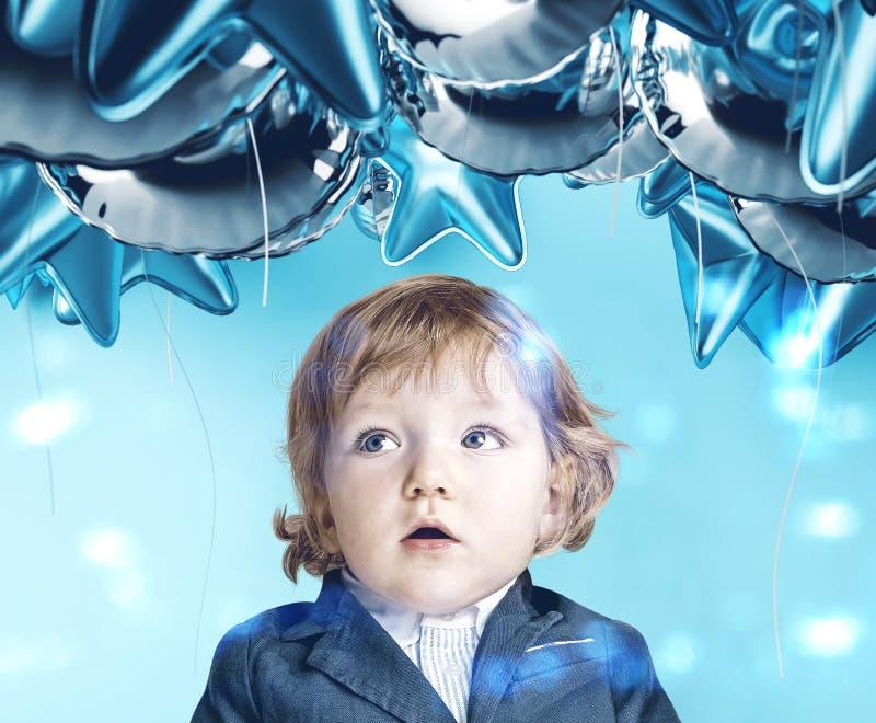 Verbaasde weinig jongen die blauwe ballons bekijken royalty-vrije stock fotografie