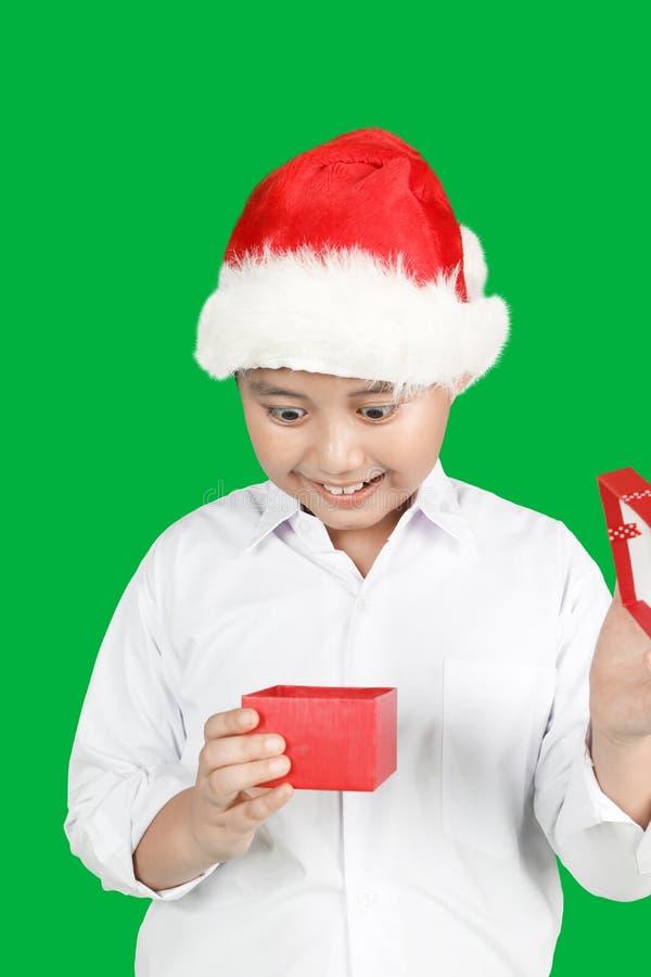 Verbaasde weinig jongen opent Kerstmisgift stock afbeeldingen