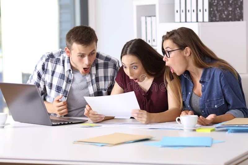 Verbaasde werknemers die een document lezen op kantoor stock afbeelding