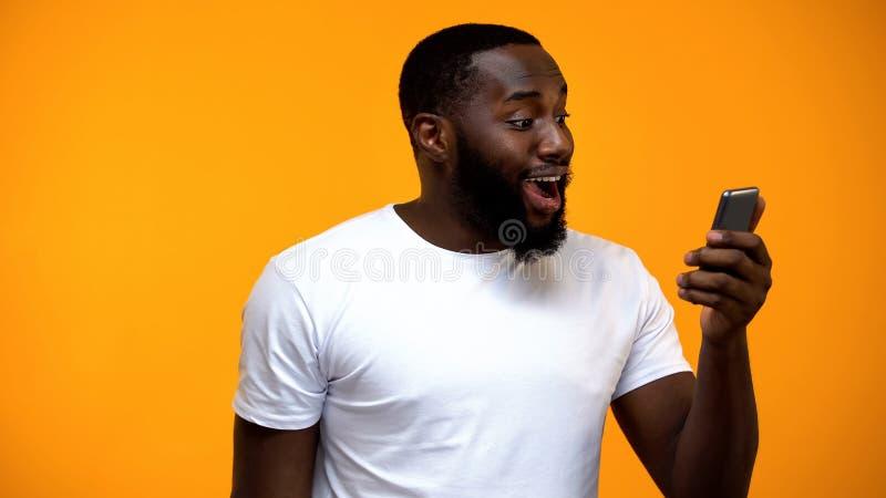Verbaasde zwarte mannelijke holdingssmartphone, de contant geld achterdiensten, online transactie royalty-vrije stock foto's