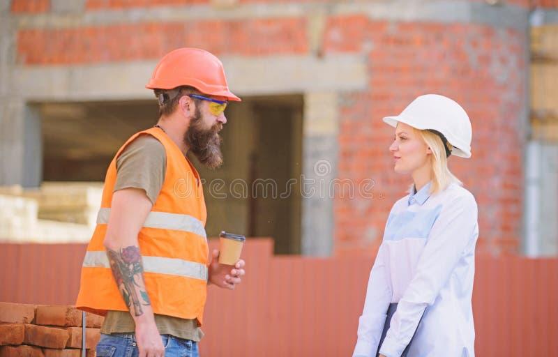 Verband tussen bouwcli?nten en deelnemers van bouwnijverheid Vrouweningenieur en brutale bouwer stock fotografie
