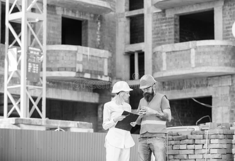 Verband tussen van bouwcliënten en deelnemers bouwnijverheid De de vrouweningenieur en bouwer communiceren bij stock afbeelding