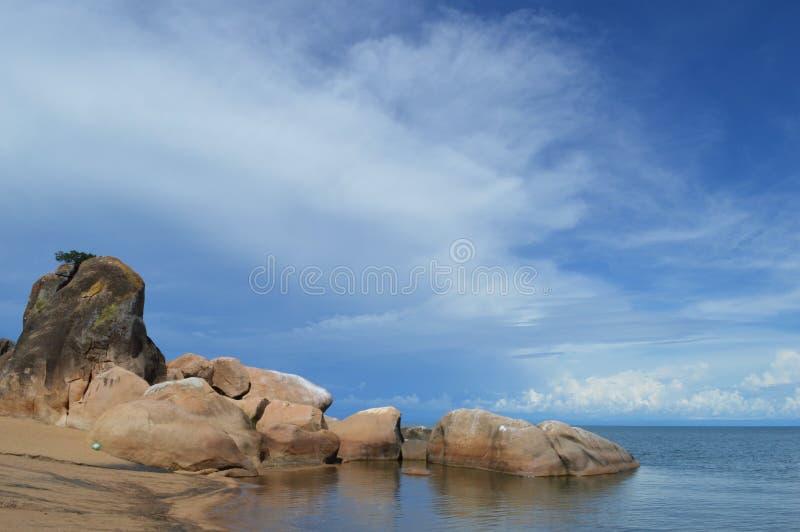 Verbazend blauw die meer Malawi of Nyasa door stenen op het strand in Afrika wordt omringd stock fotografie