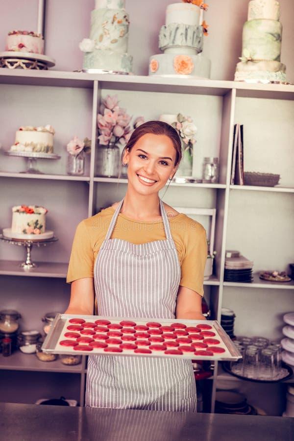 Verbazend donkerbruin meisje het aantonen dienblad met macarons royalty-vrije stock fotografie
