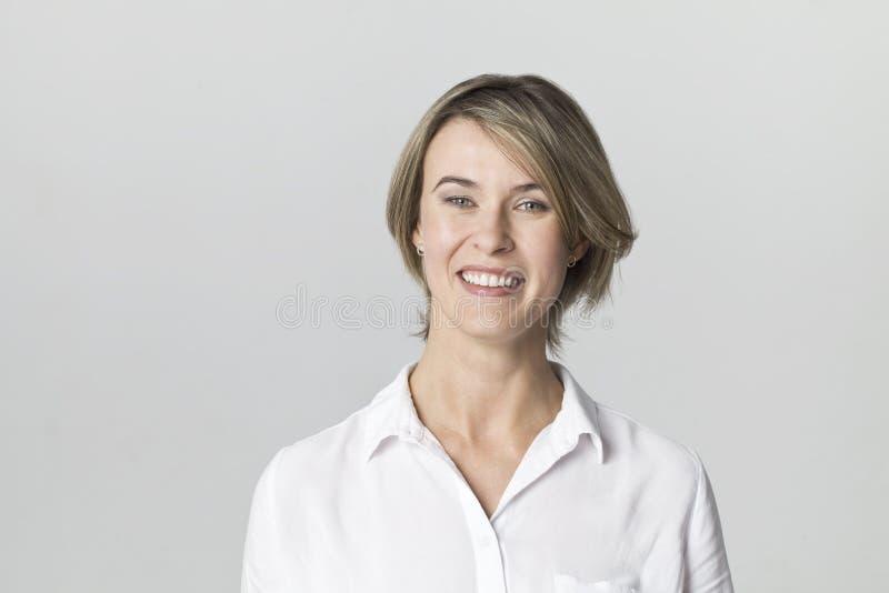 Verbazend en vrolijk glimlachend blonde in het witte die schot van de overhemdsstudio, op wit wordt geïsoleerd stock fotografie