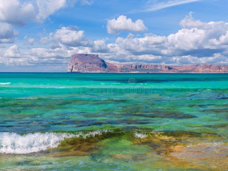 Verbazend glashelder blauw water op een paradijsstrand - kleine golf - rotsachtig eiland op de achtergrond royalty-vrije stock afbeeldingen