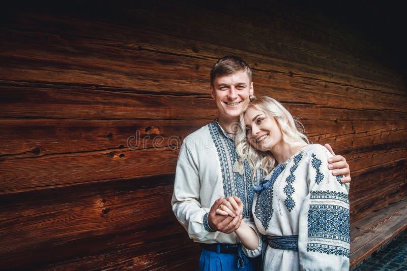 Verbazend huwelijkspaar die en handen op een achtergrond van een blokhuis glimlachen houden stock fotografie