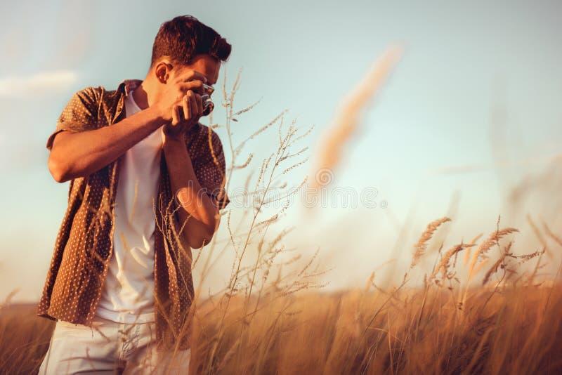 Verbazend mening van de knappe jonge mens met uitstekende camera, neem een beeld op gebiedsachtergrond, op zonsondergang royalty-vrije stock foto's