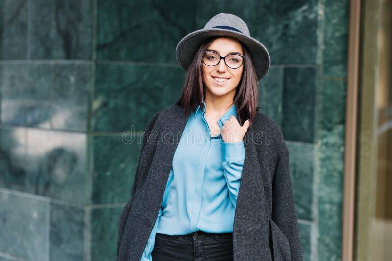 Verbazend modieuze jonge vrouw in blauw overhemd, grijze laag, hoed lopen openlucht op straat in stad Donkerbruin zwart haar, royalty-vrije stock foto's