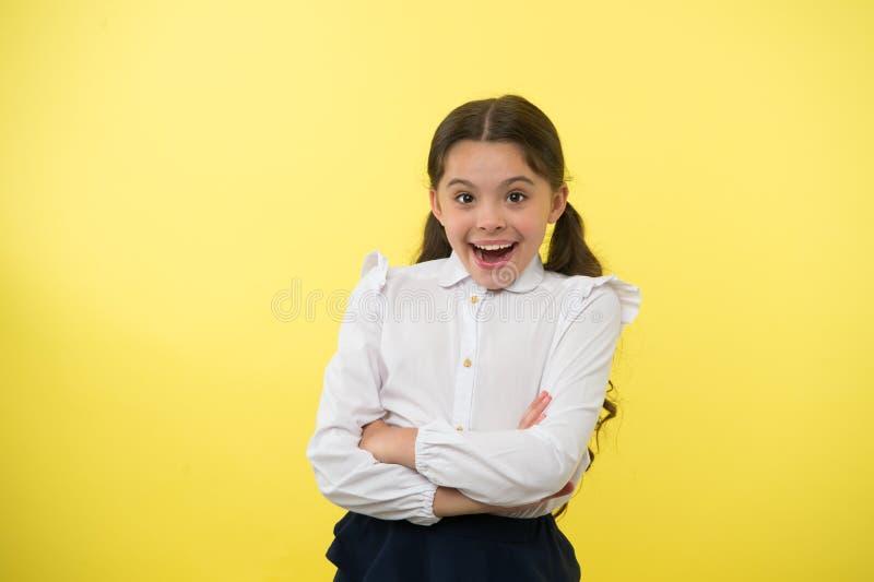Verbazend nieuws Meisjesschool eenvormig het glimlachen vrolijk gezicht die gele achtergrond benieuwd zijn Kind terug naar school stock afbeelding