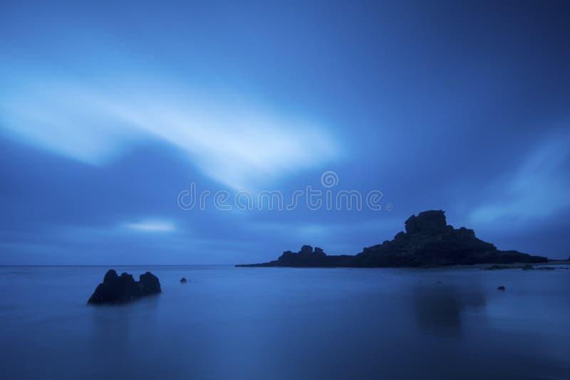 Verbazend oceaanlandschap nacht en water lige wolken en mist Rotsen in het midden van het overzees lange blootstelling met binnen royalty-vrije stock fotografie