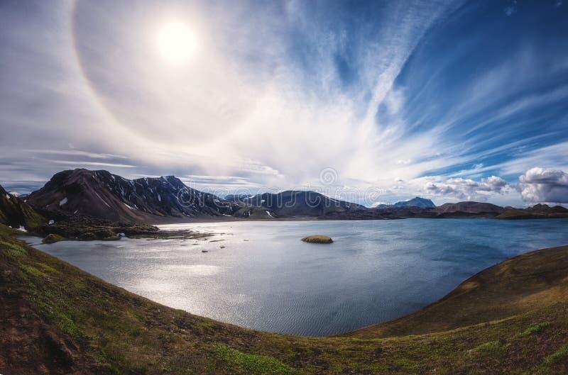 Verbazend panoramisch landschap, Hooglanden van IJsland met meer in vulkanische bergen, blauwe bewolkte hemel en zonnehalo, IJsla royalty-vrije stock afbeelding