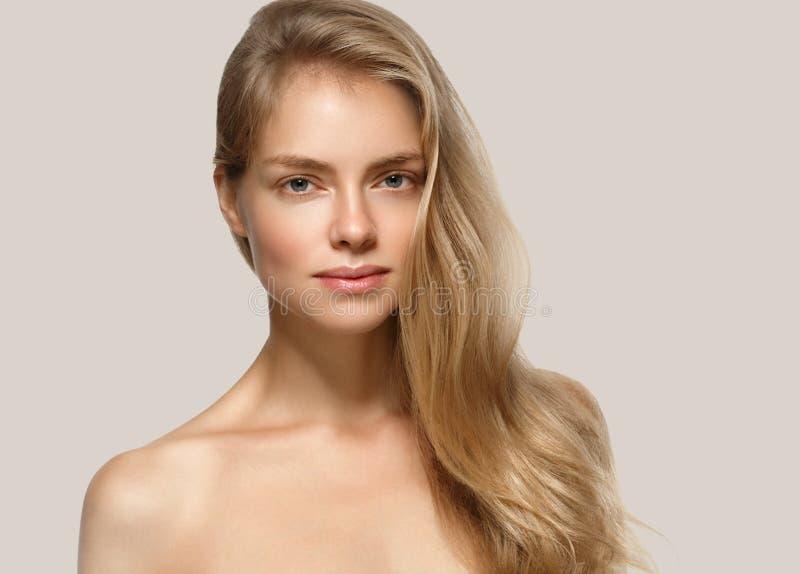 Verbazend vrouwenportret Mooi meisje met lang golvend haar Blondemodel met kapsel over beige stock afbeeldingen
