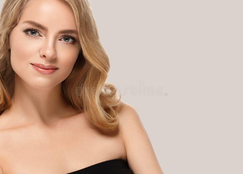 Verbazend vrouwenportret Mooi meisje met lang golvend haar Blondemodel met kapsel over beige stock foto's