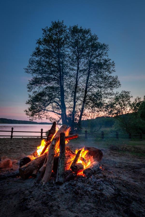 Verbazend vuur bij schemer door het meer in de zomer stock afbeelding