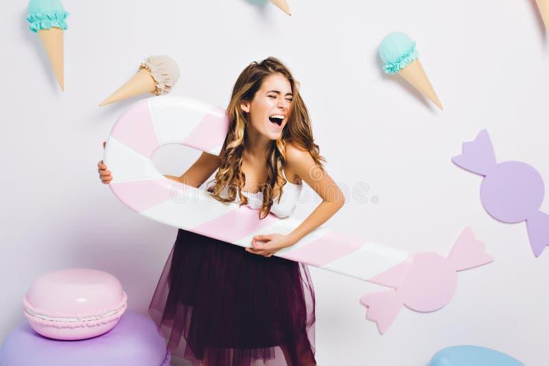 Verbazend zoet-tandmeisje dat door stuk speelgoed snoepjes wordt omringd die pret bij partij en het zingen hebben Portret van jon stock afbeeldingen
