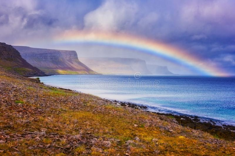 Verbazende aard, het toneellandschap van de dagtijd met regenboog over de oceaan, klippen en dramatische bewolkte hemel, Atlantis royalty-vrije stock foto