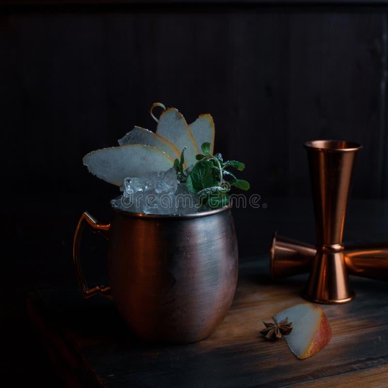 Verbazende alcoholische cocktail met wodka met stroop en stukken van ijs met plakken van verse zoete peer en kaneel in een metaal royalty-vrije stock foto's