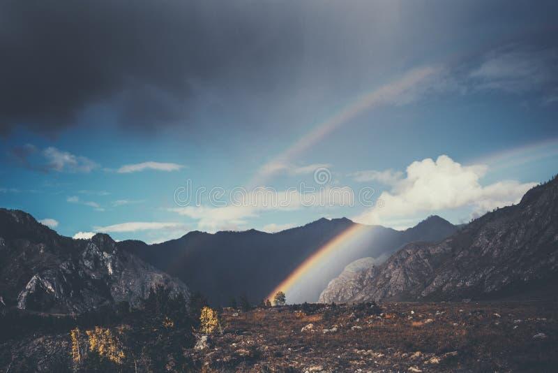 Verbazende dubbele regenboog in bergen stock foto's