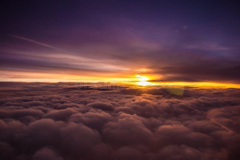 Verbazende en mooie zonsondergang boven de wolken met dramatische wolken royalty-vrije stock afbeelding