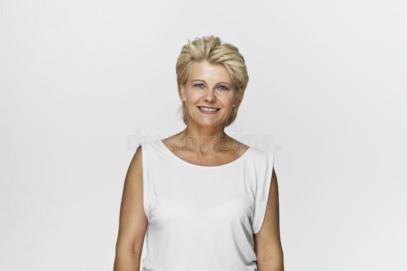 Verbazende en vrolijke glimlachende blondeonderneemster in het mooie die schot van de kledingsstudio, op wit wordt geïsoleerd stock foto