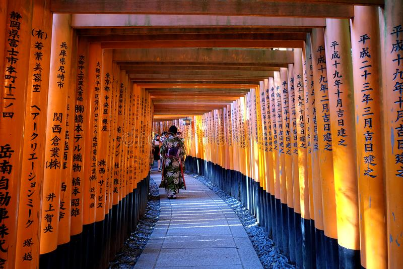 Verbazende houten oranje kleurenpoort met het citaat van Japan in zijn zij en Japans meisje die kimono dragen stock foto's