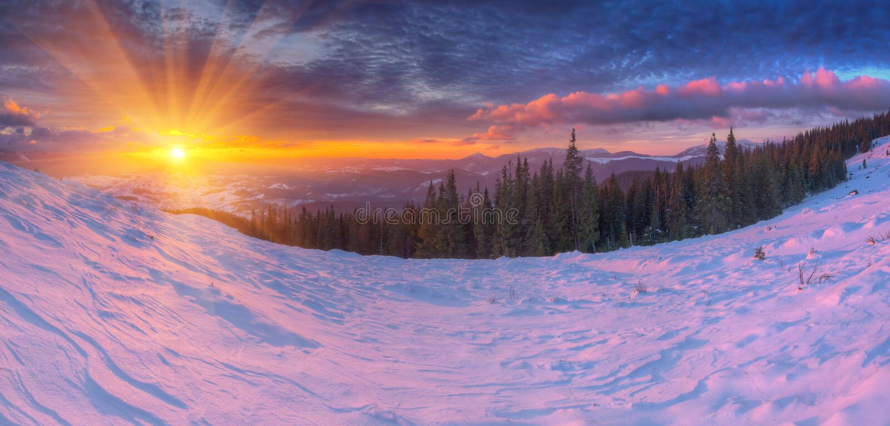 Verbazende kleurrijke zonsopgang in bergen met gekleurde wolken en roze sneeuw op voorgrond Dramatische de winterscène met sneeuw stock afbeelding