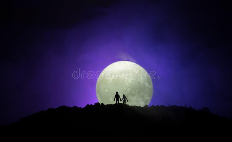 Verbazende liefdescène Silhouetten van jong romantisch paar die zich onder het maanlicht bevinden royalty-vrije stock fotografie