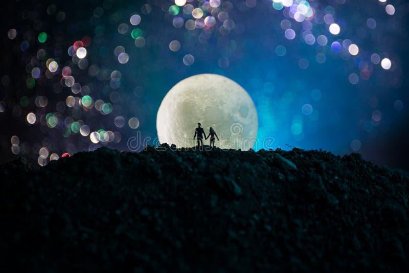 Verbazende liefdescène Silhouetten van jong romantisch paar die zich onder het maanlicht bevinden stock foto's