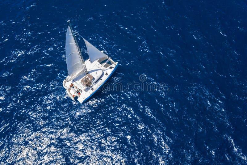 Verbazende mening aan Catamaran die in open zee bij winderige dag kruisen Hommelmening - de hoek van het vogelsoog stock foto
