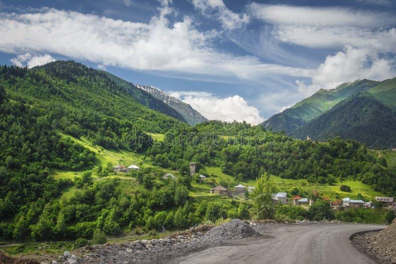 Verbazende mening over Georgisch landschap met groen grasrijk heuvels, weide, bergen en dorp op de zomer zonnige dag in Svaneti-g stock afbeeldingen
