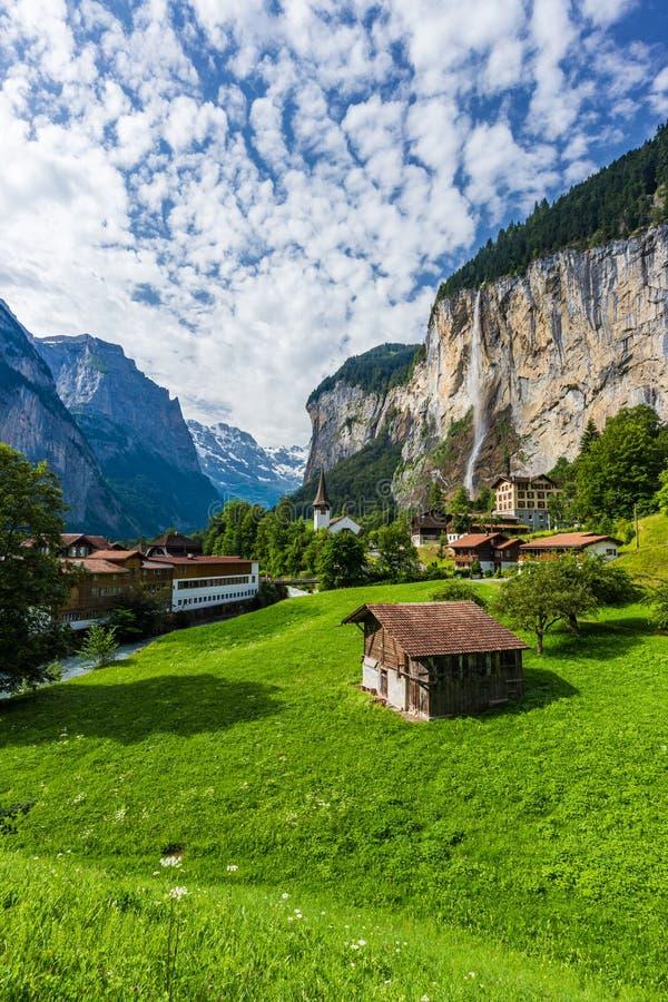 Verbazende mening van beroemde Lauterbrunnen-stad in de Zwitserse vallei van Alpen met mooie Staubbach-watervallen op de achtergr stock afbeelding