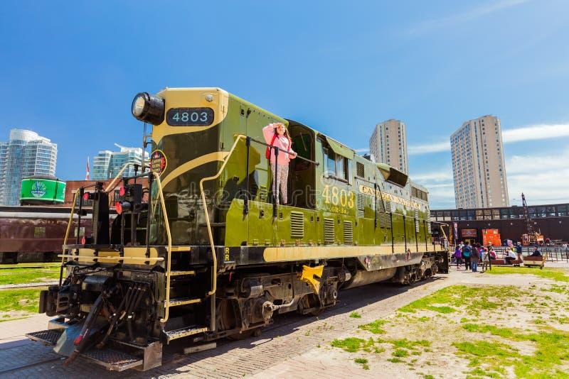 Verbazende mening van oude stijl retro diesel trein met meisje het kijken omhoog op het benedengebied van het stadsdistrict op zo royalty-vrije stock foto's