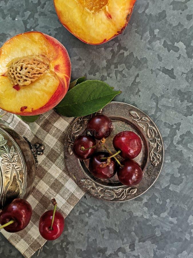 Verbazende mening van perziken en kersen op de lijst Heldere, sappige vruchten - perziken en kersen stock foto's