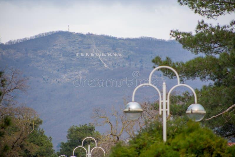 Verbazende mooie mening van bergen met inschrijving 'Gelendzhik 'van stadssteeg met mooie lantaarns en groene bomen stock fotografie