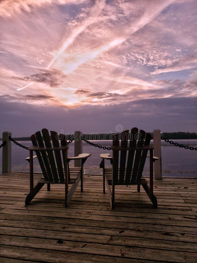 Verbazende purpere oever van het meerzonsondergang met twee stoelen op een dok royalty-vrije stock foto