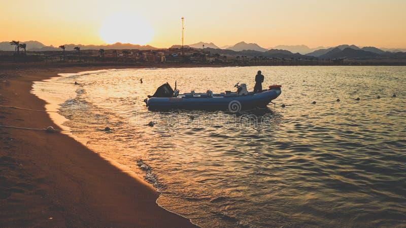 Verbazende silhouetfoto van opblaasbare boot met motor die op kalme oceaangolven bij de zandige kust tegen zonsonderganghemel sch royalty-vrije stock fotografie