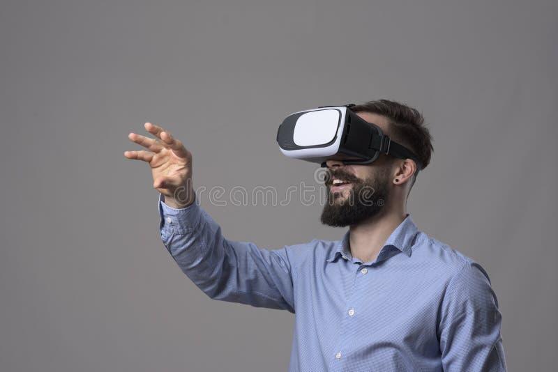 Verbazende virtuele werkelijkheidservaring van de jonge bedrijfsmens die vr glazen met de hand dragen en het scherm gesturing stock foto