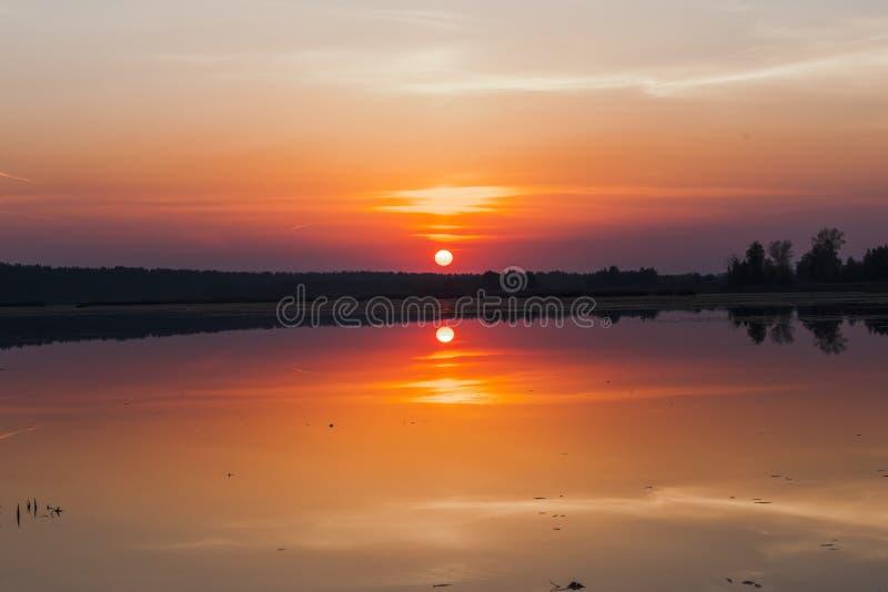 Verbazende zonsondergang over het meer Kleurrijke bezinning in het water stock fotografie