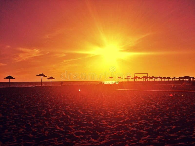 Verbazende zonsondergang, strand en strandparaplu's Ada Bojana, Montenegro stock afbeelding