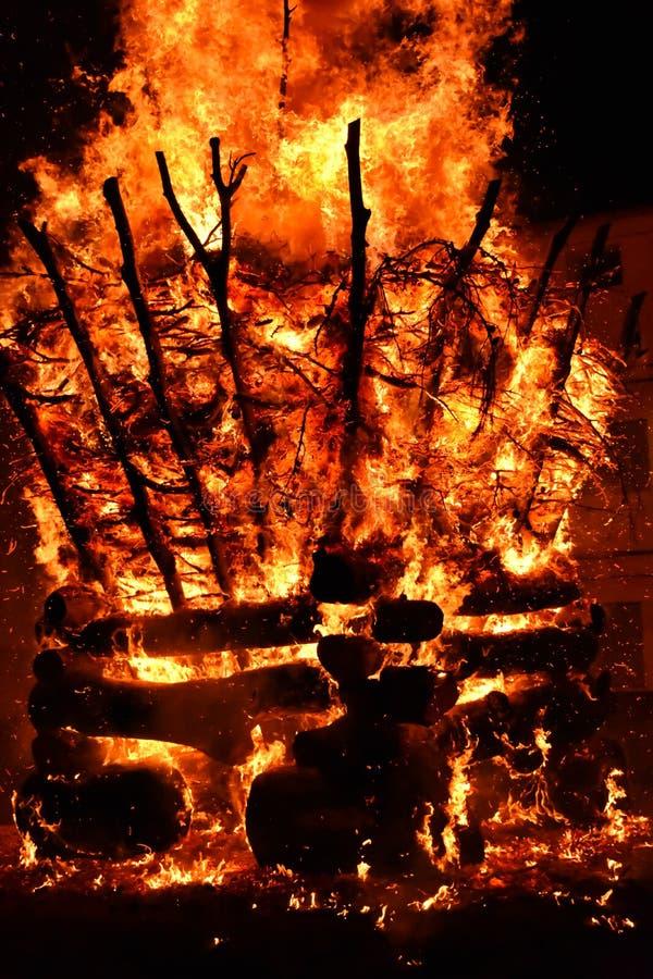 verbazingwekkende brand in een dorp in de donkere nacht De verbranding van brandhout leidt tot grote vlammen, vlammen, rook, gas stock fotografie