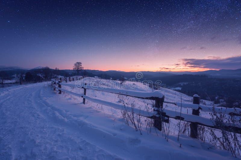Verbazingwekkende natuur bergt landschap, winterpad 's nachts met sneeuw en mooie blauwe hemel met sterren en gloed van zonsonder royalty-vrije stock afbeeldingen