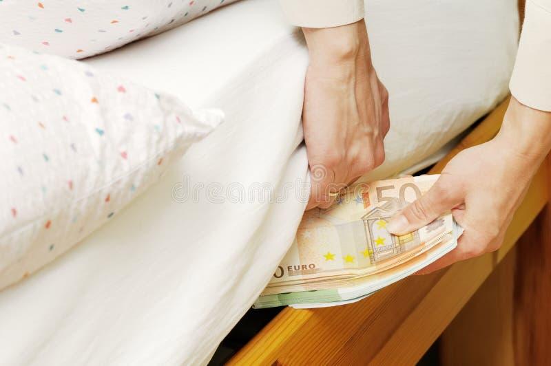 Verbergend geld onder matras stock afbeelding