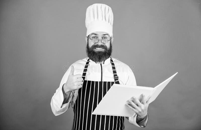Verbeter het koken vaardigheid Boekrecepten Volgens recept Kokende voedsel van de mensen het gebaarde chef-kok Culinair Kunstenco stock foto's
