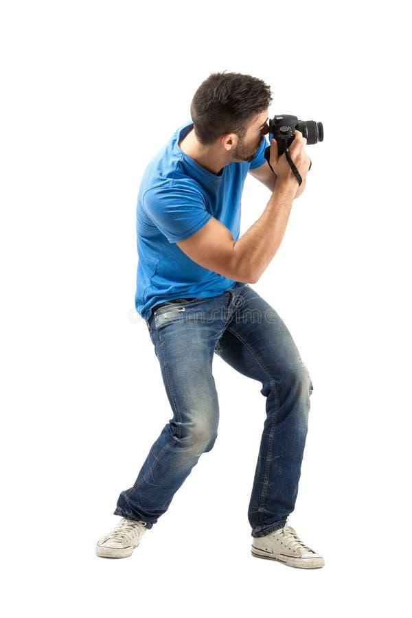 Verbiegen Sie den jungen Mann, der Foto mit Seitenansicht der Digitalkamera macht stockfotografie