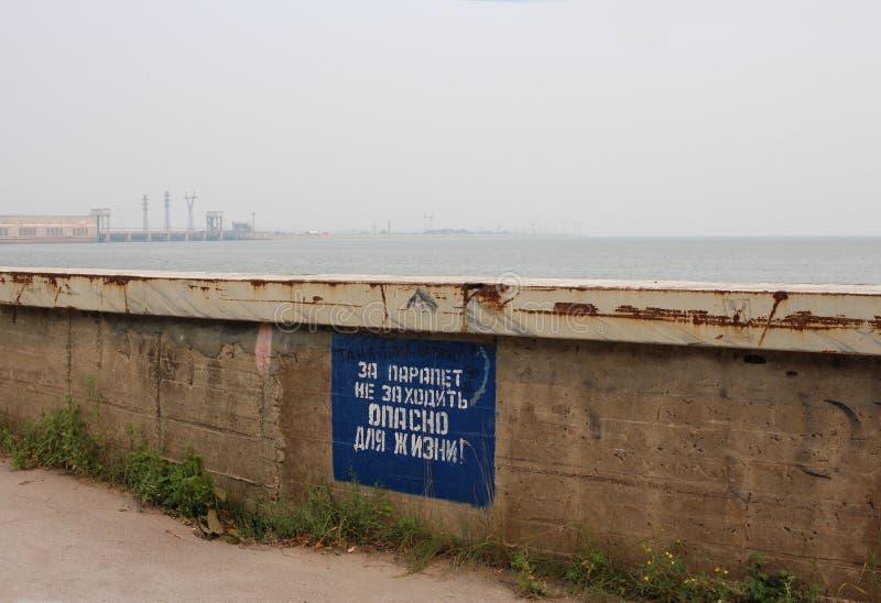 Verbieten der Aufschrift auf der Platte: das Geländer ist nicht für das Leben auf der Ufergegend nahe der hydroelektrischen Energ lizenzfreie stockfotografie