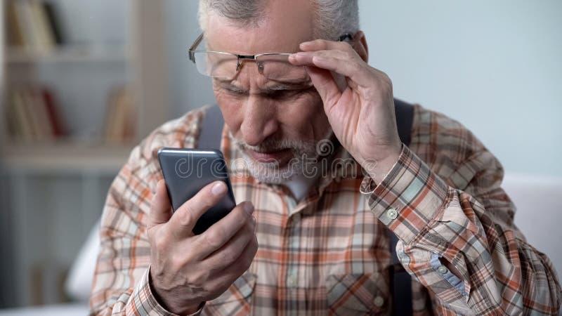 Verbijsterde oude mens die cellphone, nieuwe technologie bekijken ingewikkeld voor bejaarden royalty-vrije stock foto's