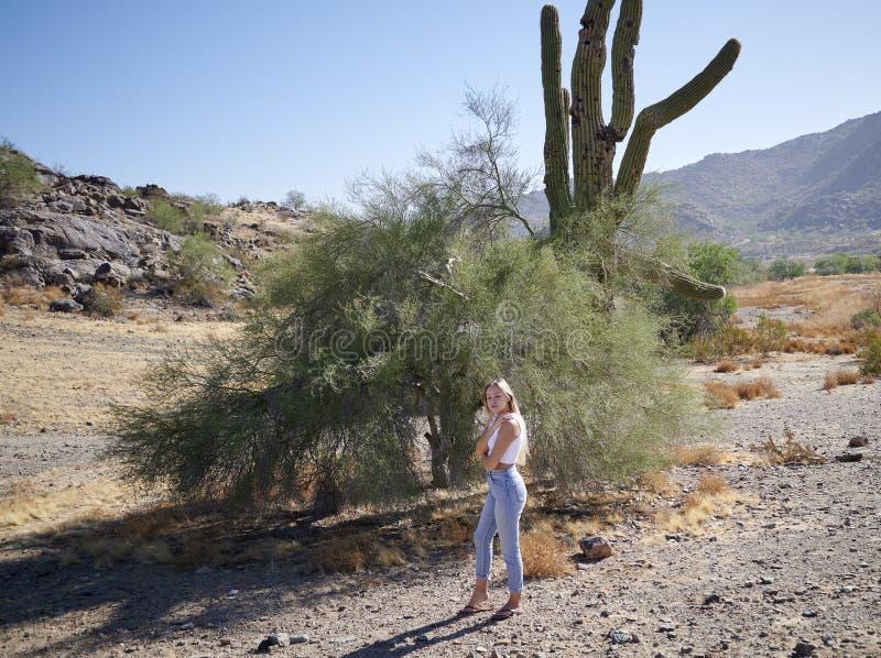 Verbijsterend jonge Latina-vrouw stelt zich voor in de witte tank en denim - woestijn stock foto