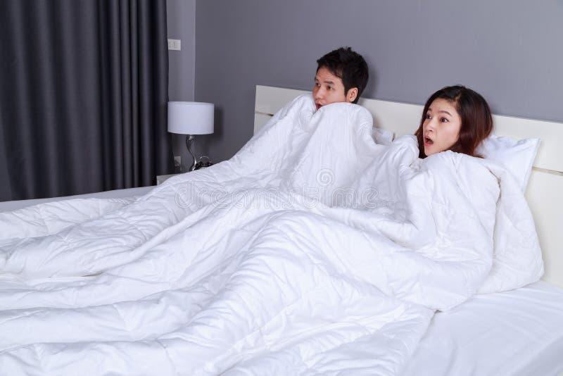 Verbinden Sie aufpassenden erschrockenen Film unter der Decke auf Bett lizenzfreie stockfotos