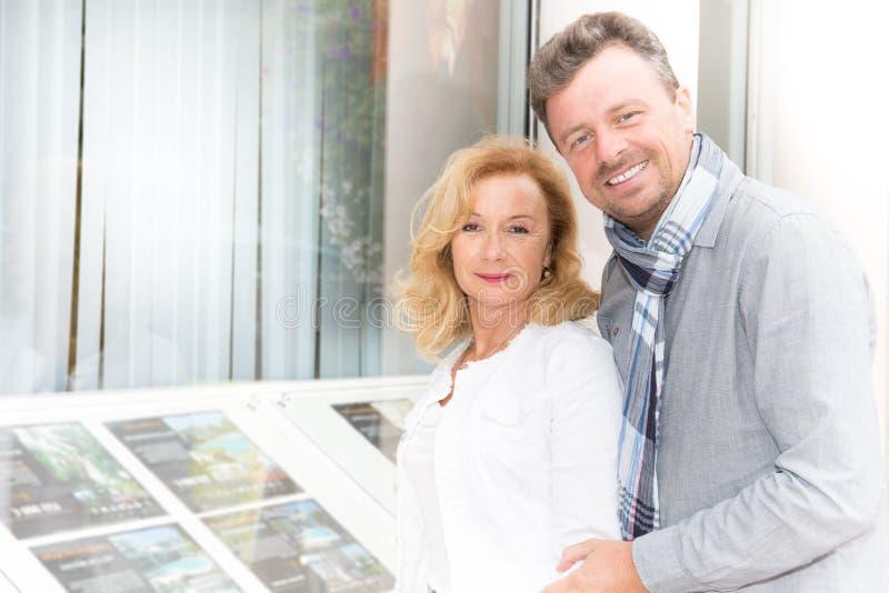 verbinden Sie Blick am Fenster einer Immobilienagentur, um zu kaufen stockbild